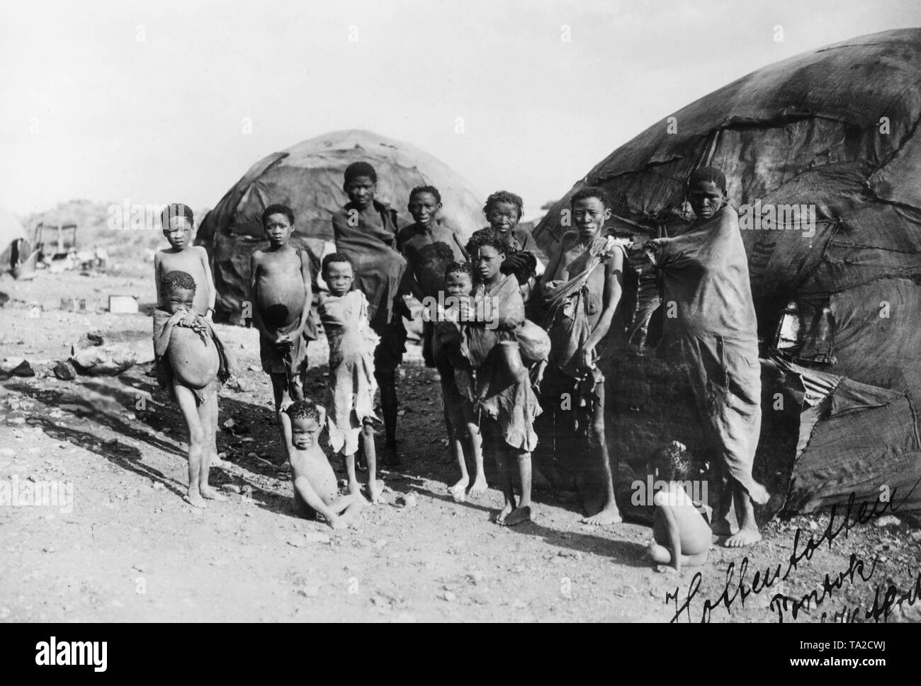 Children of Hottentots of different ages are partially wrapped in thin blankets in front of a pondok in German Southwest Africa. Children and adults show signs of malnutrition like bloated stomach and are emaciated. The image is undated and bears a print date of 1939. - Stock Image