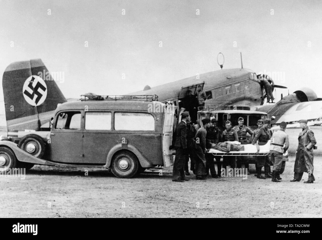 Photo of a wounded soldier of The Condor Legion, who is brought by comrades on a stretcher from an ambulance car to an air ambulance (Junkers Ju 72) of the German Lufthansa. A large swastika is displayed on the vertical tail. - Stock Image