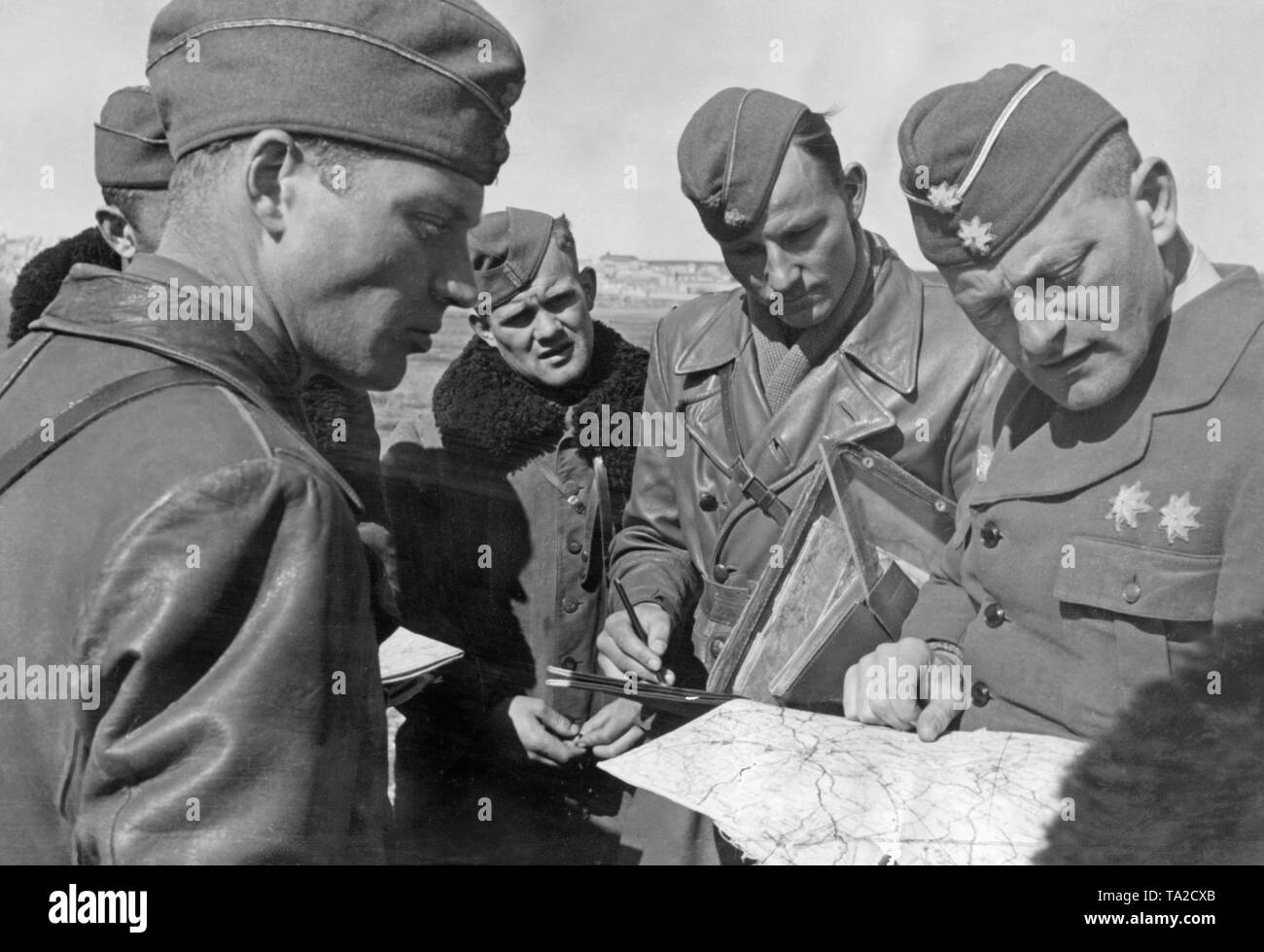 Undated photo of a briefing of combat pilots of the Condor Legion during the Spanish Civil War in 1939. A Major (right) shows the pilots their operational areas on a map. - Stock Image