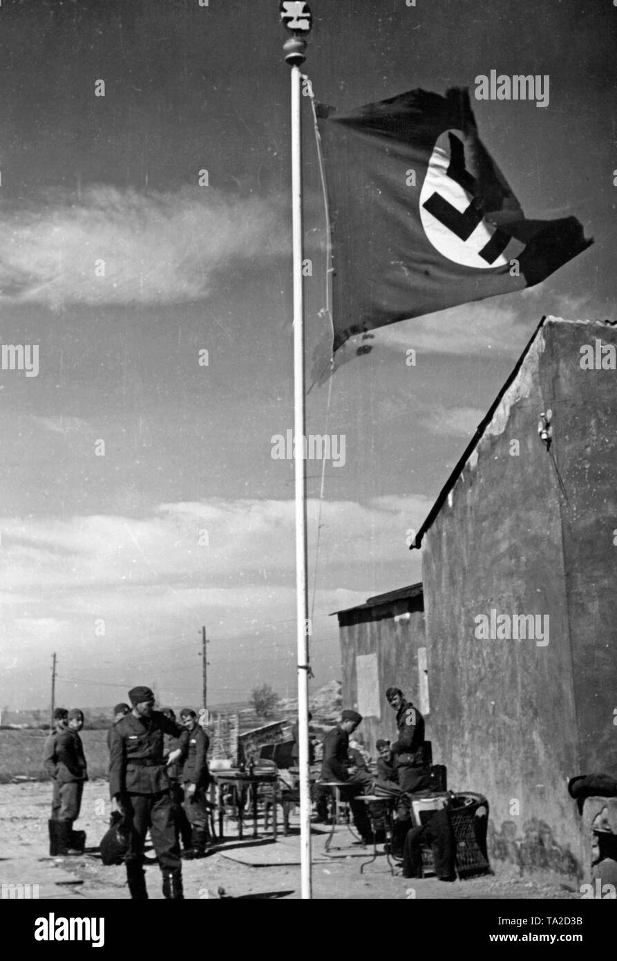 Photo of a flagpole with a swastika of the bomber squadron of the combat group 88 at an airfield. In the background, soldiers of the squadron. On top of the flagpole the squadron badge (eagle performing nosedive with bomb, hull cockade). - Stock Image
