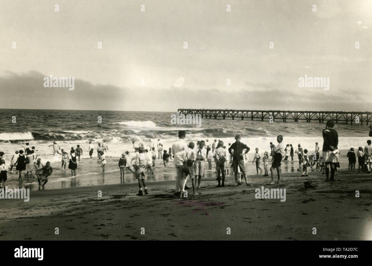 German children play and swim on the beach in Swakopmund, German South West Africa. In the background the landing stage 'Jetty'. - Stock Image