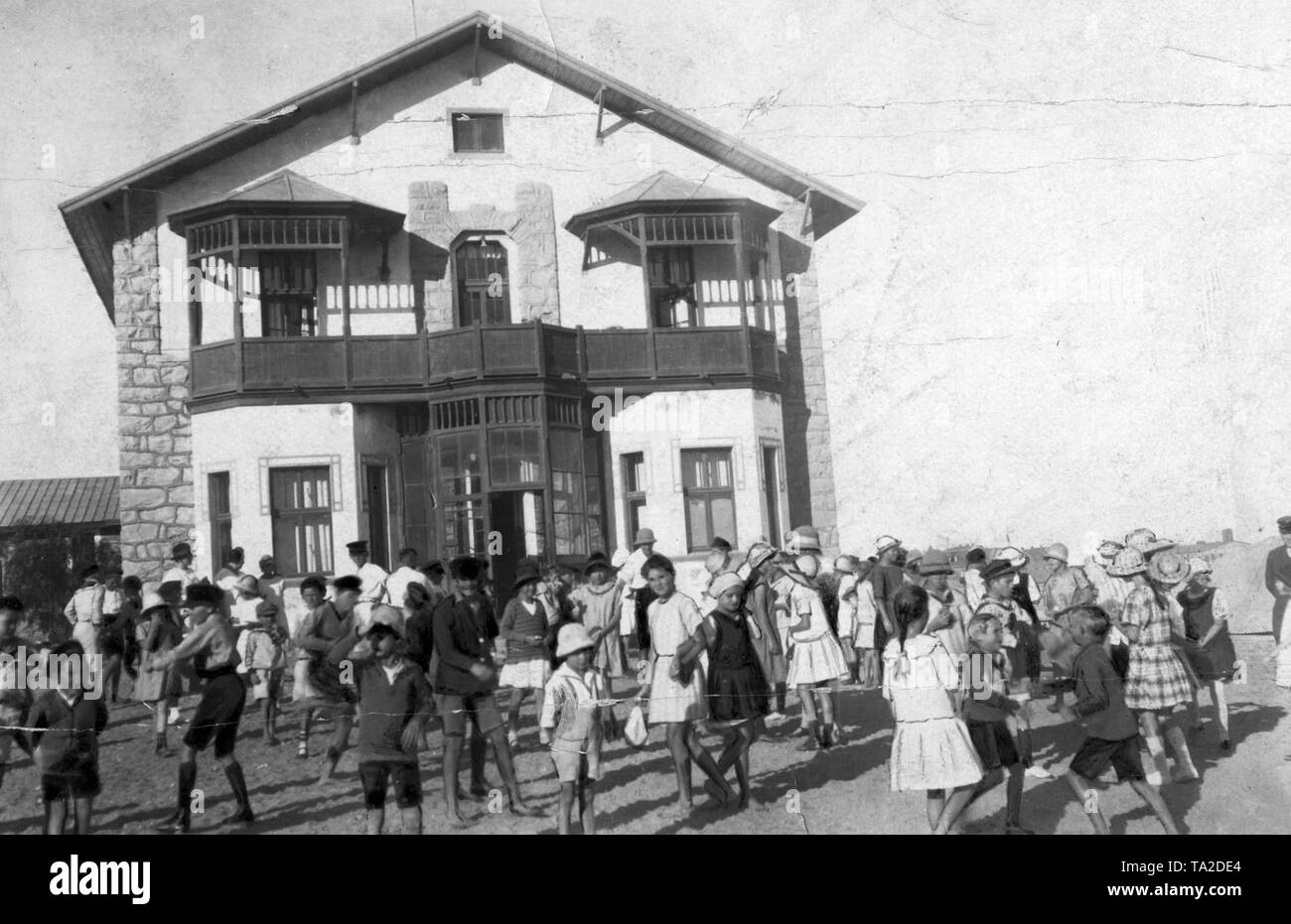 German children play in front of the building of the German School in Luederitz Bay, German South-West Africa. - Stock Image
