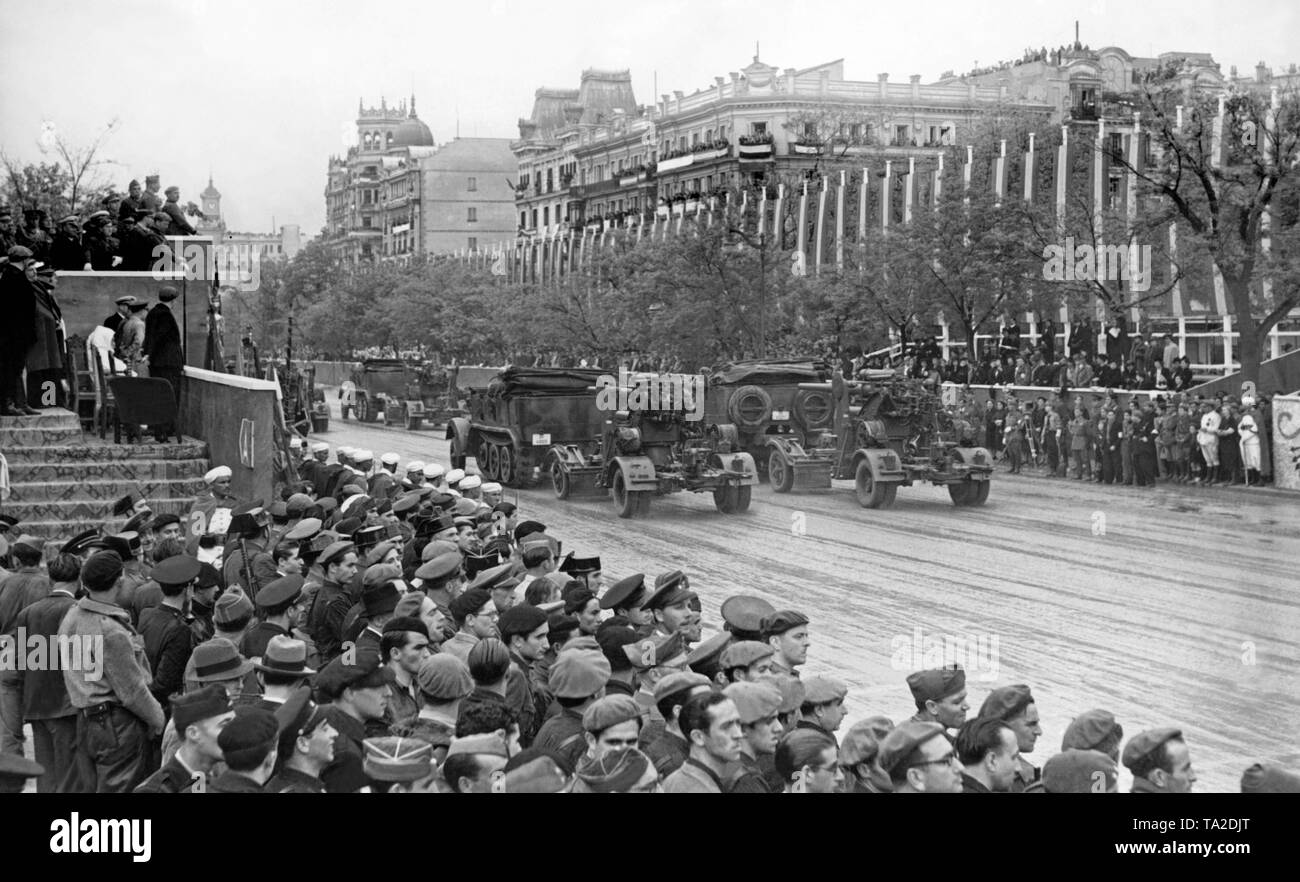 A scene of the victory parade of General Franco in Madrid on May 21, 1939 a month after the end of the war. Here the parade of an antiaircraft unit with a 8.8cm (88mm) flak of the Legion Condor. On the left of the balcony are Franco and the commander of the Legion Generalmajor Wolfram Freiherr von Richthofen. - Stock Image