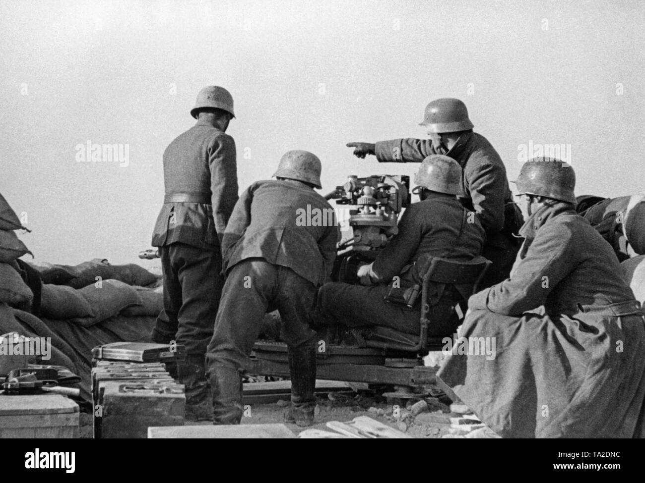 Undated photo of an anti-aircraft unit of the Condor Legion during the deployment in the Spanish Civil War. Five men are taking aim at ground targets with a 2cm FLAK 39 in a sandbag position. On the left in the front there are crates of ammunition. The soldiers are wearing M35 steel helmets. - Stock Image