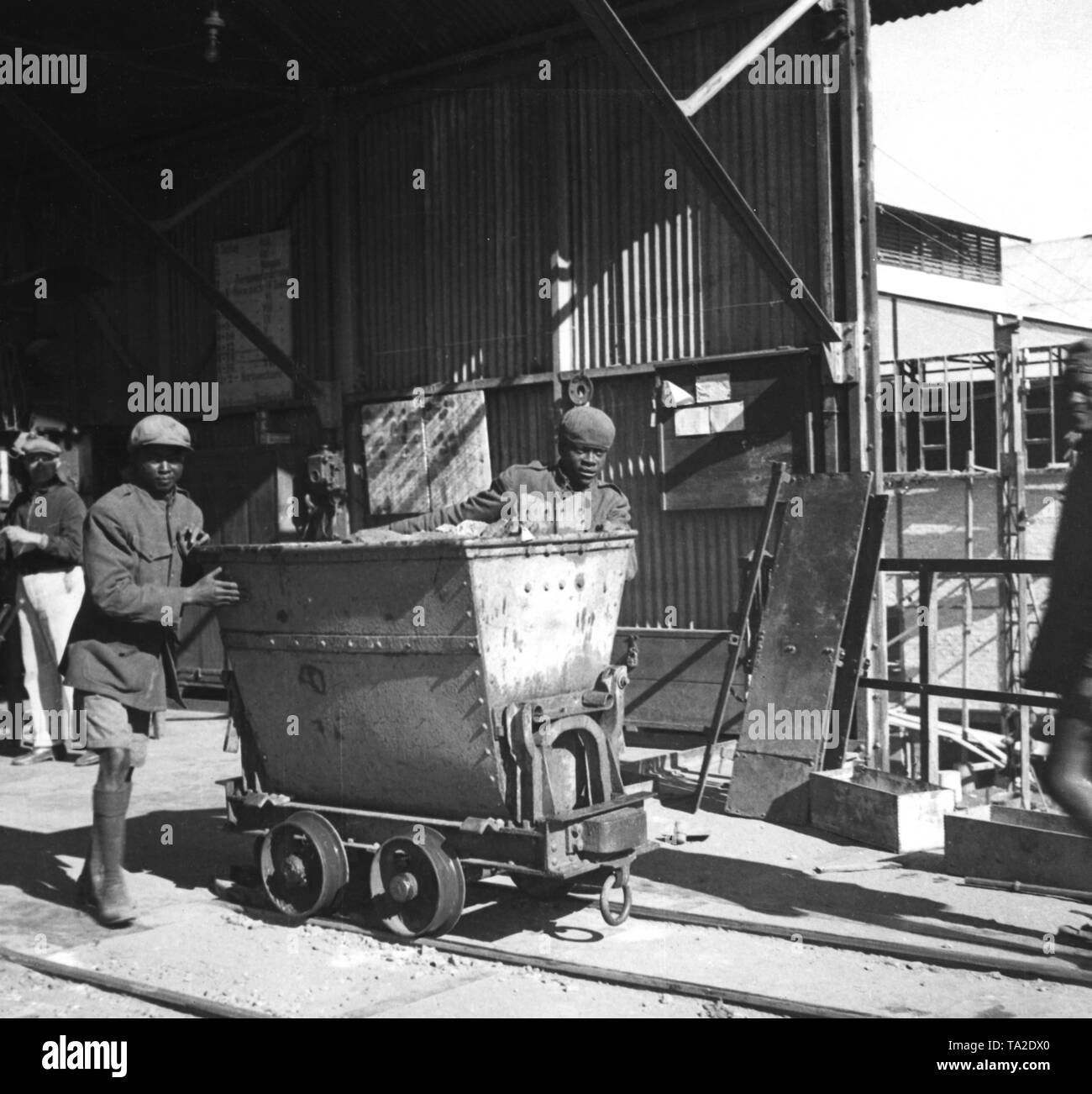 Two workers in the Tsumeb mine push an ore wagon out of the hoist frame (undated shot). - Stock Image
