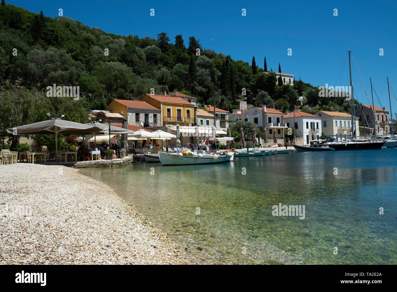 Boats and yachts in the bay at Kioni, Ithaca, Greece. Ithaca, Ithaki or Ithaka is a Greek island located in the Ionian Sea to the west of continental Greece. Ithacas main island has an area of 96 square kilometres. It is the second-smallest of seven main Ionian Islands. - Stock Image
