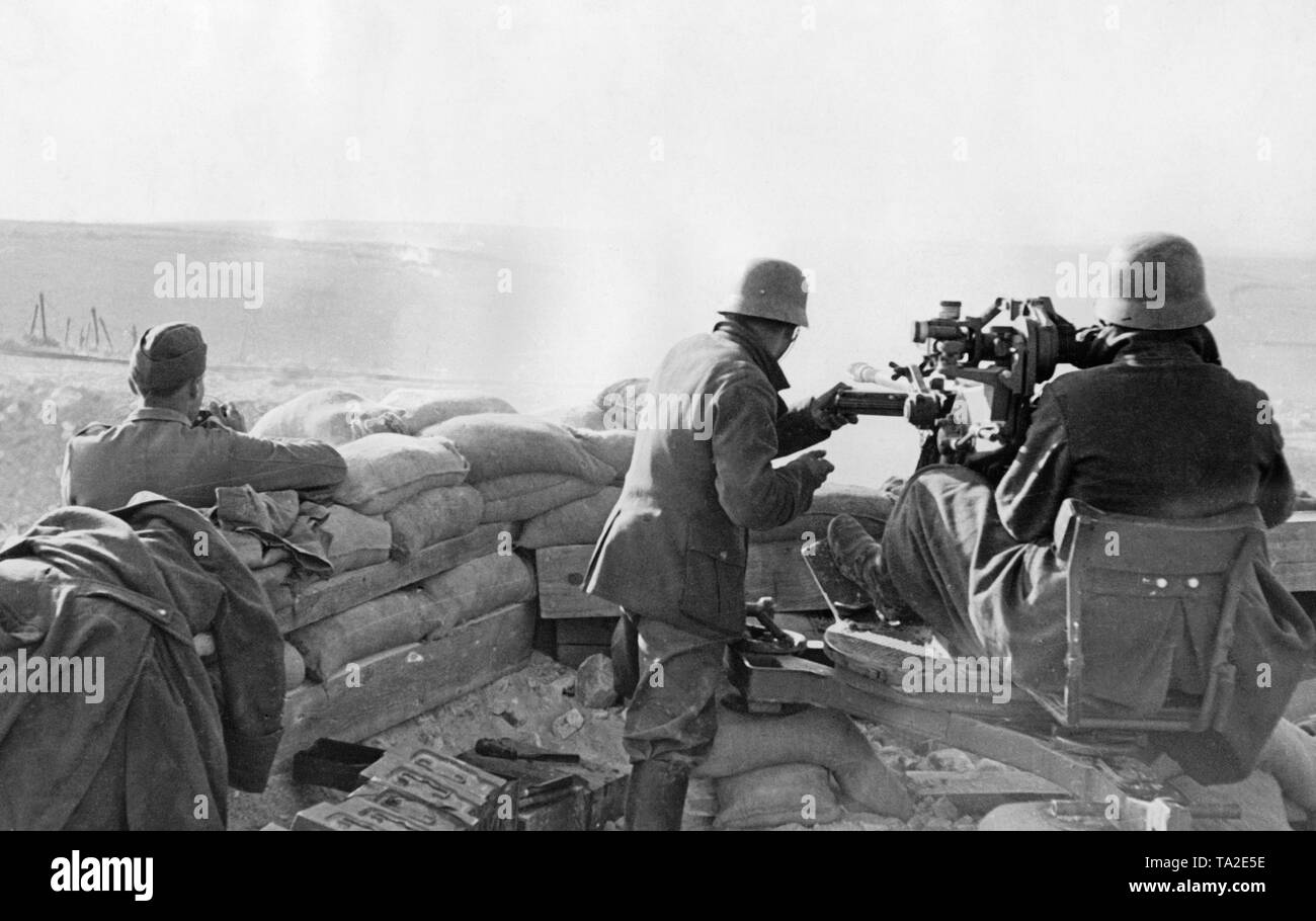 Undated photo of an antiaircraft unit of the Condor Legion during a deployment in the Spanish Civil War. Two men are aiming at ground target using a 2cm FLAK 39 in a sandbag position. An officer (left) picks the targets. On the left in the front, there are crates of ammunition. The soldiers are wearing M35 steel helmets. - Stock Image