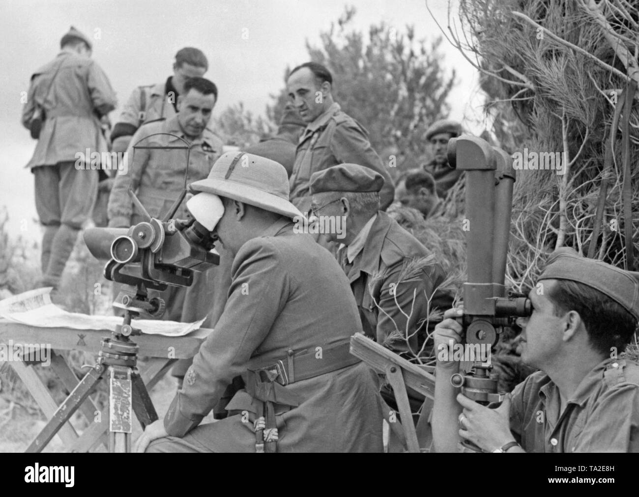 Photo of Generalissimo Francisco Franco (in the front with a topee, looking through a German headlight 35, Flakglas 10x80) together with General Emilio Mola Vidal (behind, with a beret and field tunic) during the visit of officers of a division of the Condor Legion in the Spanish Civil War before June, 1937. A legionary is looking through a scissors telescope. Behind the generals, a card table and staff officers. - Stock Image