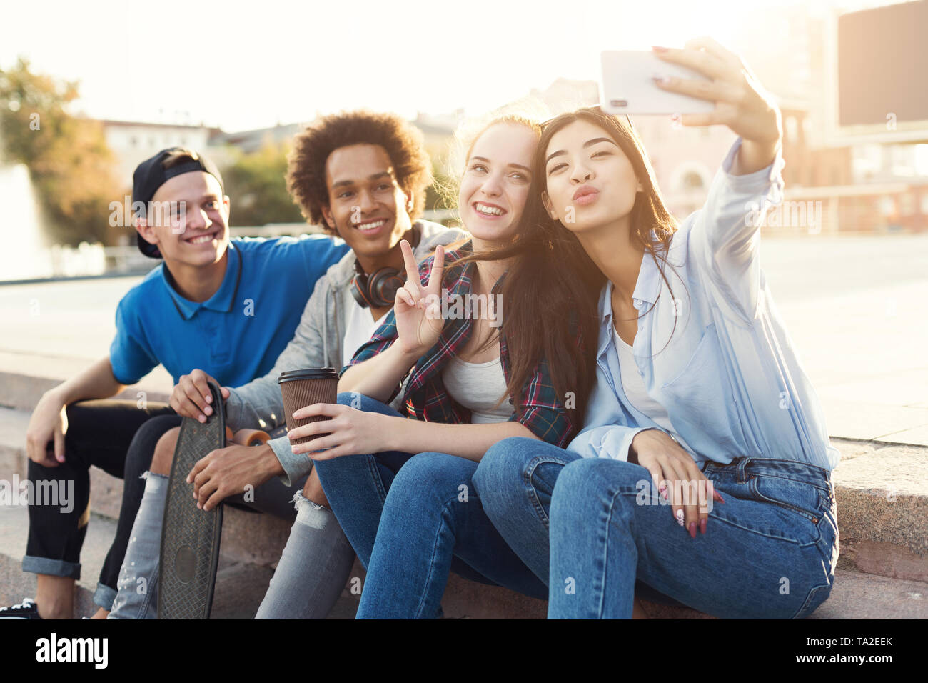 Group of multiethnic teenagers taking selfie, sitting on stairs - Stock Image