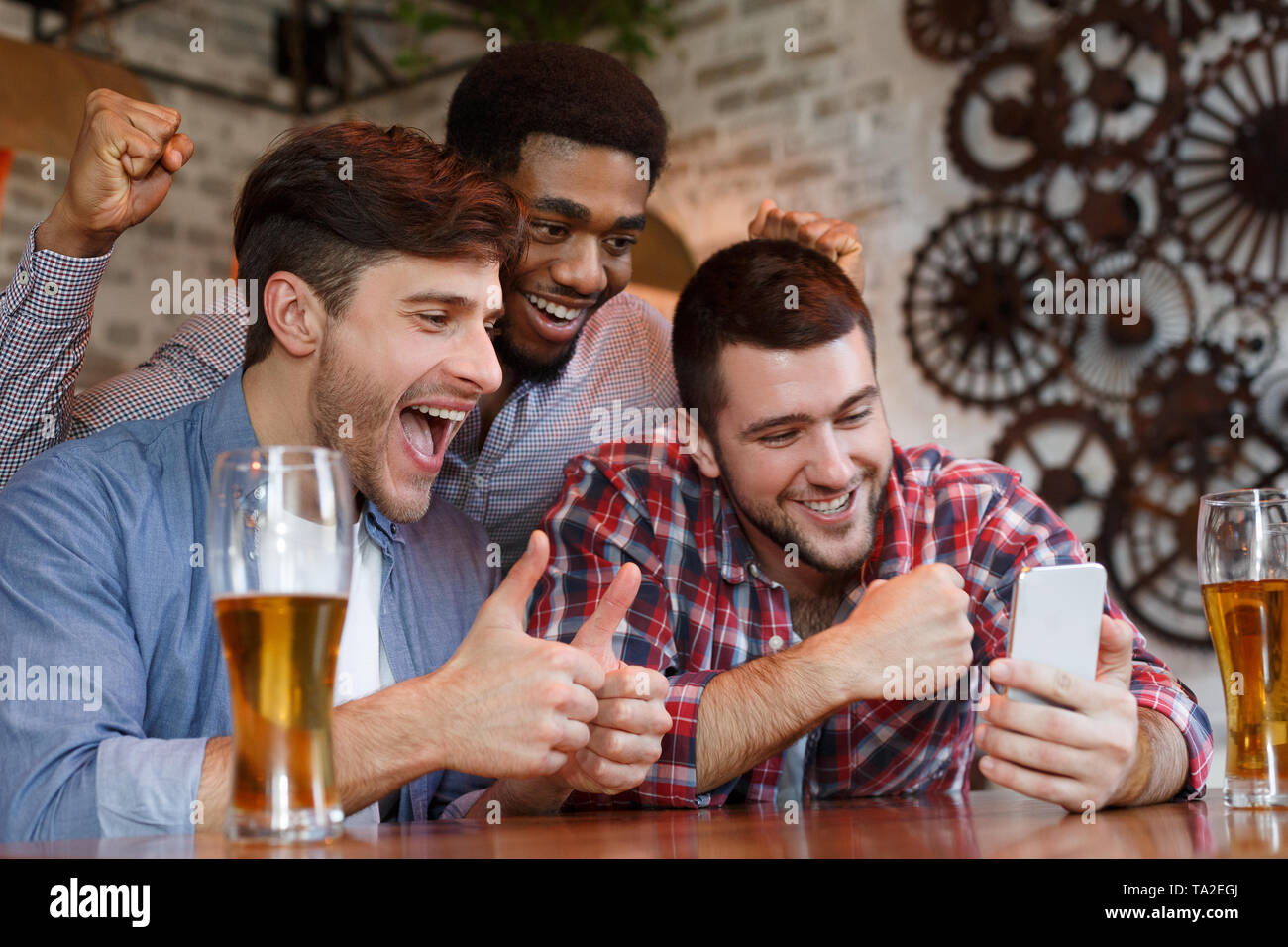 Male Friends Having Video-Call On Smartphone In Bar - Stock Image