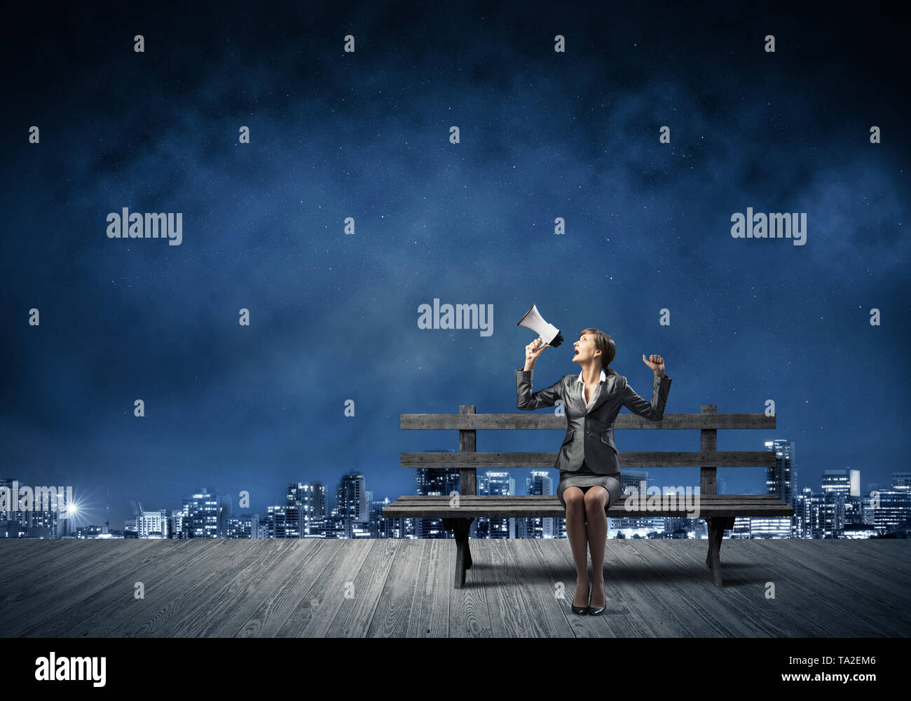 Business woman with megaphone on wooden bench - Stock Image