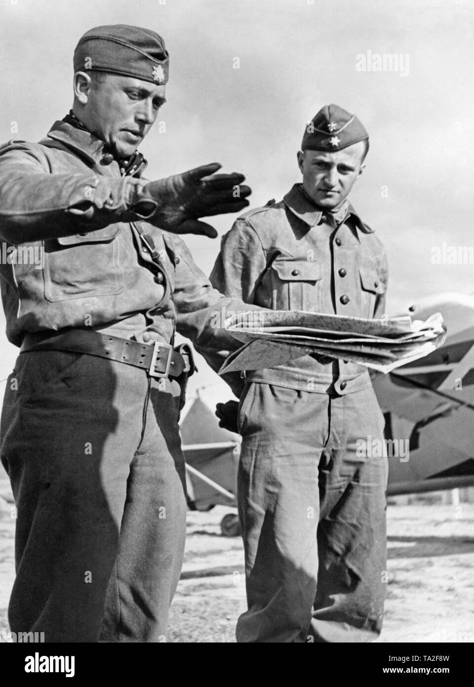 Photo of a captain (left), who is explaining his attack to a lieutenant (right) with a map. Both officers are wearing leather flight suits. - Stock Image