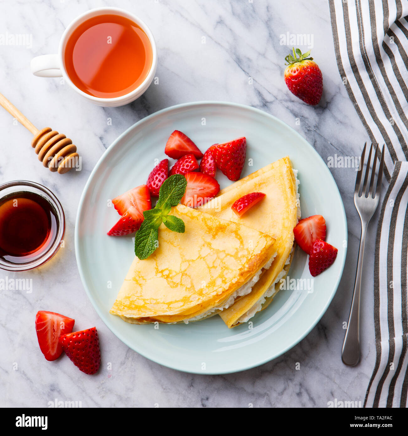 Crepes, thin pancakes with cream cheese, ricotta and fresh strawberries. Marble background. Top view. - Stock Image