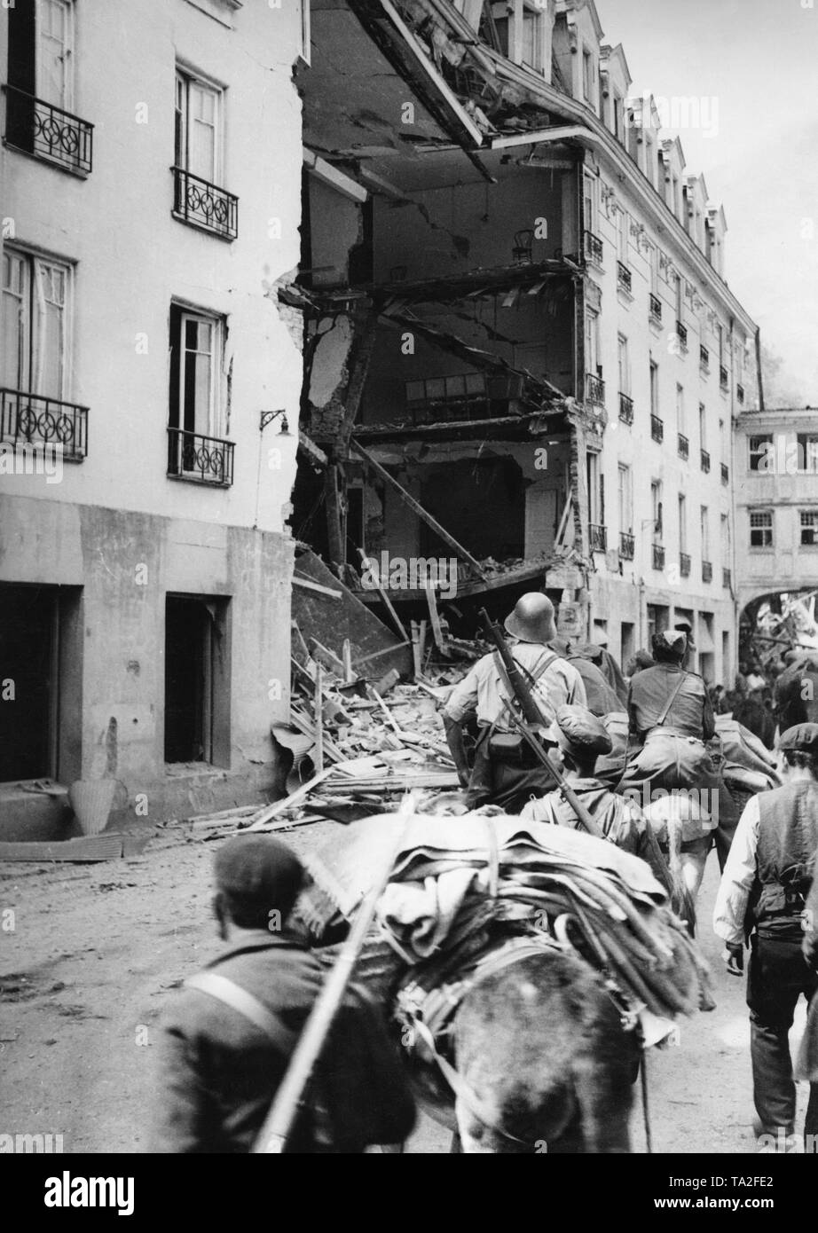 PhotoofSpanish nationalsoldiers when entering the captured Santander, Cantabria, Spanish Atlantic coast on August 27, 1937. In the foreground, armed soldiers andpack animalswith carabiners. Two soldiers ride on donkeys. In the background, a residential house, presumablypartly demolishedby a bombshell. - Stock Image