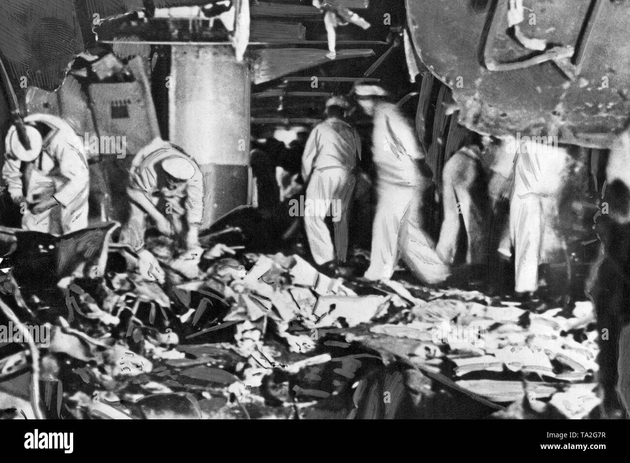 Photoof sailors during acleaning-upoperation on the deck of 'Deutschland' after the bomb attack in the port of the Balearic Island of Ibiza on the 29th of May, 1937. In the foregroundlies debris. On top there are shattered armor plates. - Stock Image