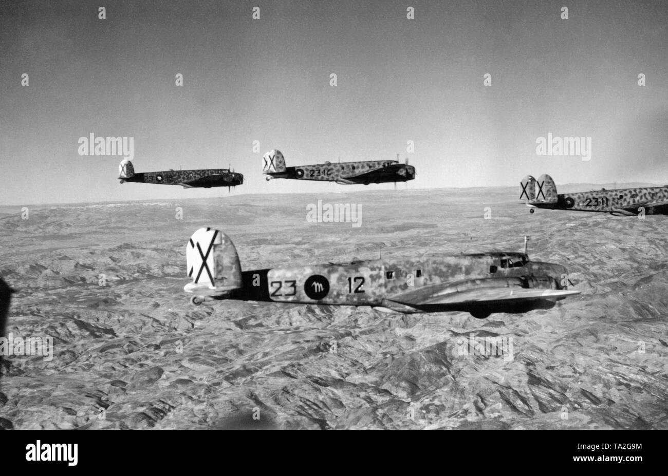 Photo of four Italian bombers, type Fiat BR.20 'Cicogna' on a Feindflug over a mountain chain in the Spanish Civil War. The cockades of the Italian Aviazione Legionaria, which resembled those of the German Condor Legion, are easily recognizable. There is a white letter M in the black cockade on the hull, which stands for the M in the signature of Benito Mussolini. - Stock Image