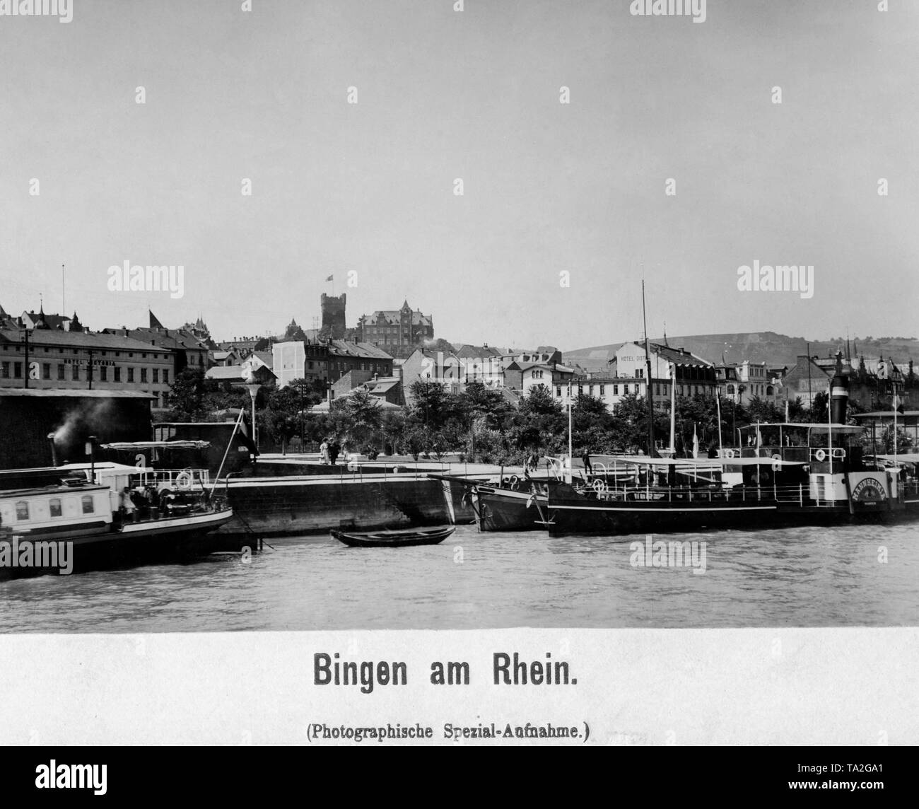 Bingen am Rhein photographed from the river, in the foreground pier with ships and in the background the Hotel Victoria, Klopp Castle and the Hotel Distel. - Stock Image