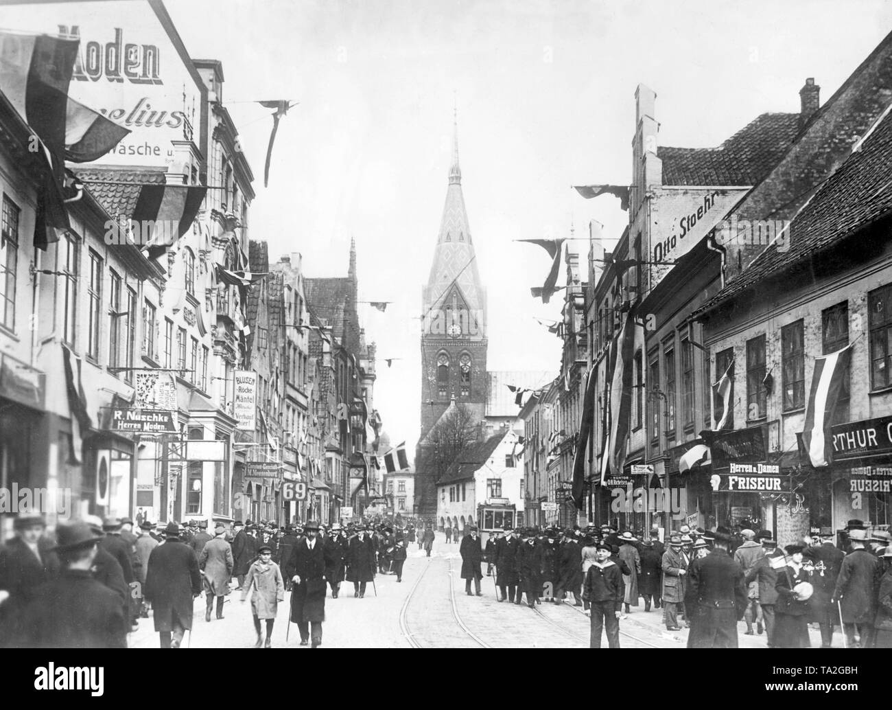 During the vote on remaining in the German Reich, the Grosse Strasse in Flensburg is full of people .The Schleswiger should vote for a stay, the black-white-red flag decoration on the buildings shows the loyalty of the Flensburg people to Germany.Only in the background on the left side of the road is a Danish flag. - Stock Image