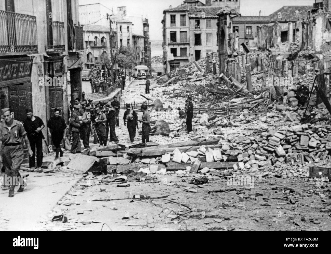 Photo of Spanish soldiers during their visit to Toldeo and the destroyed fortress of Alcazar after its liberation on September 26, 1936. The soldiers are walking through rubble in a street. In the ruins, dead horses. - Stock Image