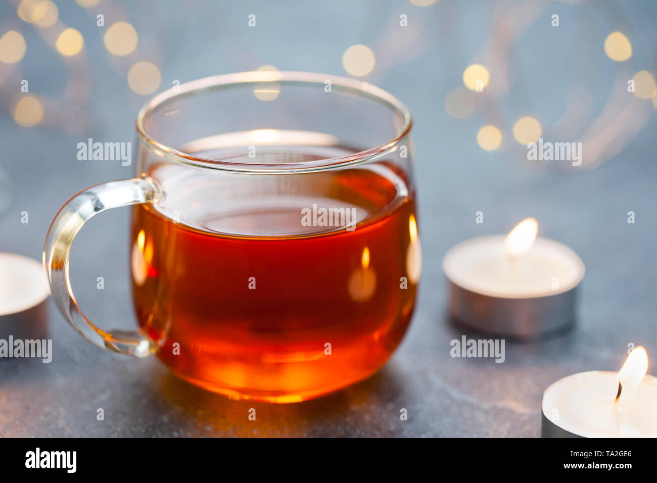Black tea in glass cup with candles and light garland. Grey background. Copy space. Stock Photo