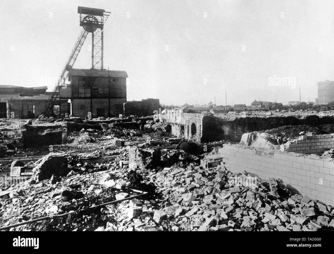 View over the ruin of the Vollmond mine in Bochum. The buildings are partially demolished or collapsed. The shaft tower is still standing. - Stock Image