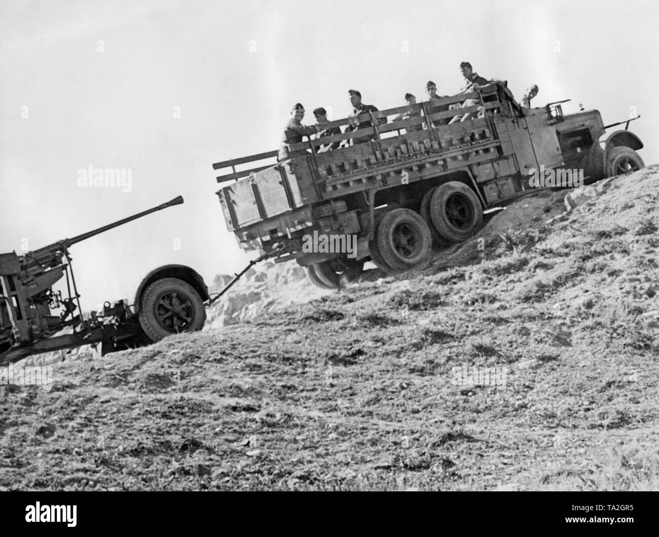 Undated photo of an anti-aircraft unit of the Condor Legion during the Spanish Civil War. The 3.7cm antiaircraft gun 18 is thereby pulled up by a truck. Legionnaires are sitting on the stillage of the truck. - Stock Image