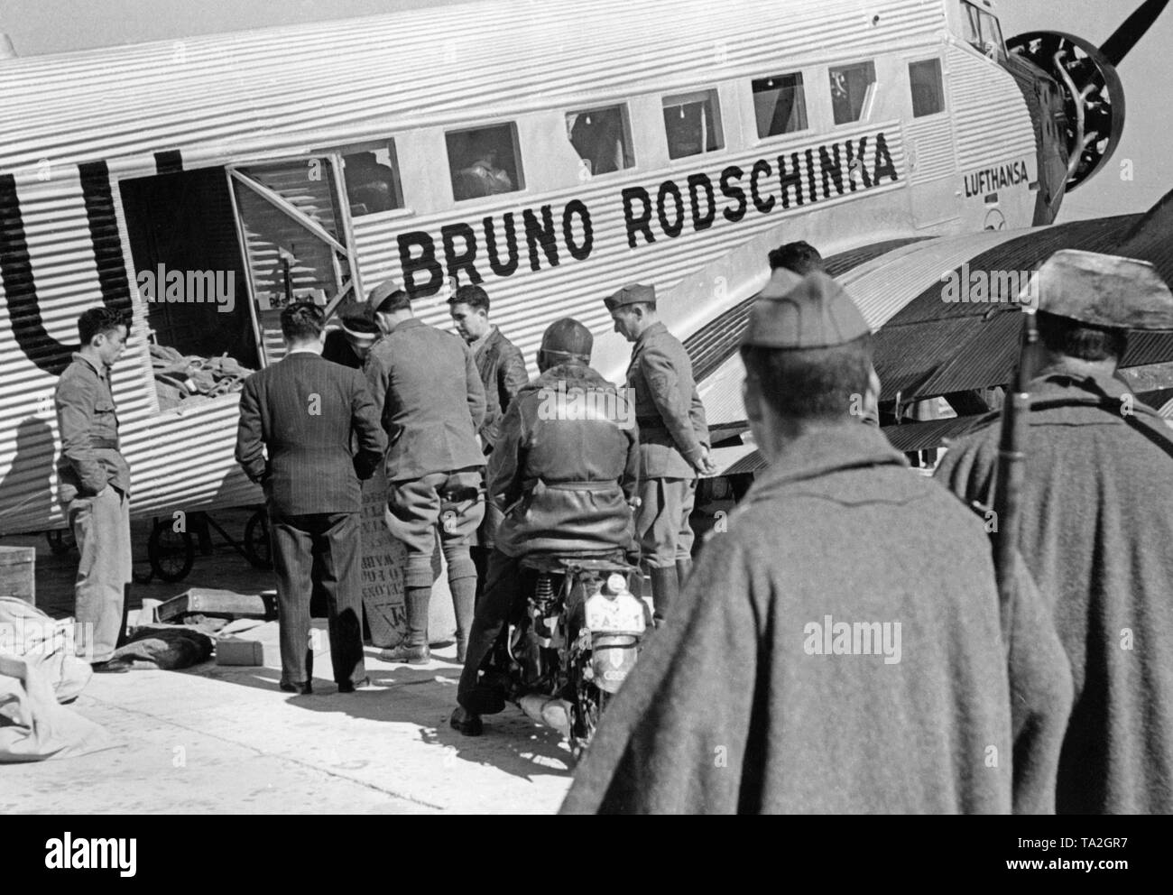 Photo of a German Junkers Ju 52 of the Deutsche Lufthansa AG 1939 at Salamanca airport, Castile and Leon, Spain. The aircraft bears the name 'Bruno Rodschinka '. It is just being loaded. In the foreground, two policemen of the Guardia Civil. During the Civil War, the Lufthansa and the Spanish Iberia (founded in 1927) carried out scheduled flights mostly with German pilots in the Spanish national zone from 1937. The aircrafts were provided by the Deutsche Lufthansa AG. - Stock Image