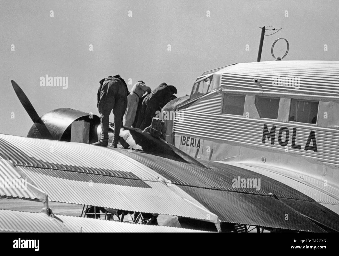 Photo of the wing, cockpits and engines of a German Junkers Ju 52 of the Spanish airline Iberia 1939 at the airport of Salamanca, Castile and Leon, Spain. Mechanics are working on one of the engines. The machine is named 'Mola', after general Emilio Mola Vidal (died 1937), one of the leaders of the uprising of General Francisco Franco. During the Civil War, the Deutsche Lufthansa and the Iberia (founded in 1927) carried out scheduled flights mostly with German pilots in the Spanish national zone from 1937. The aircraft were provided by the Deutsche Lufthansa AG. - Stock Image