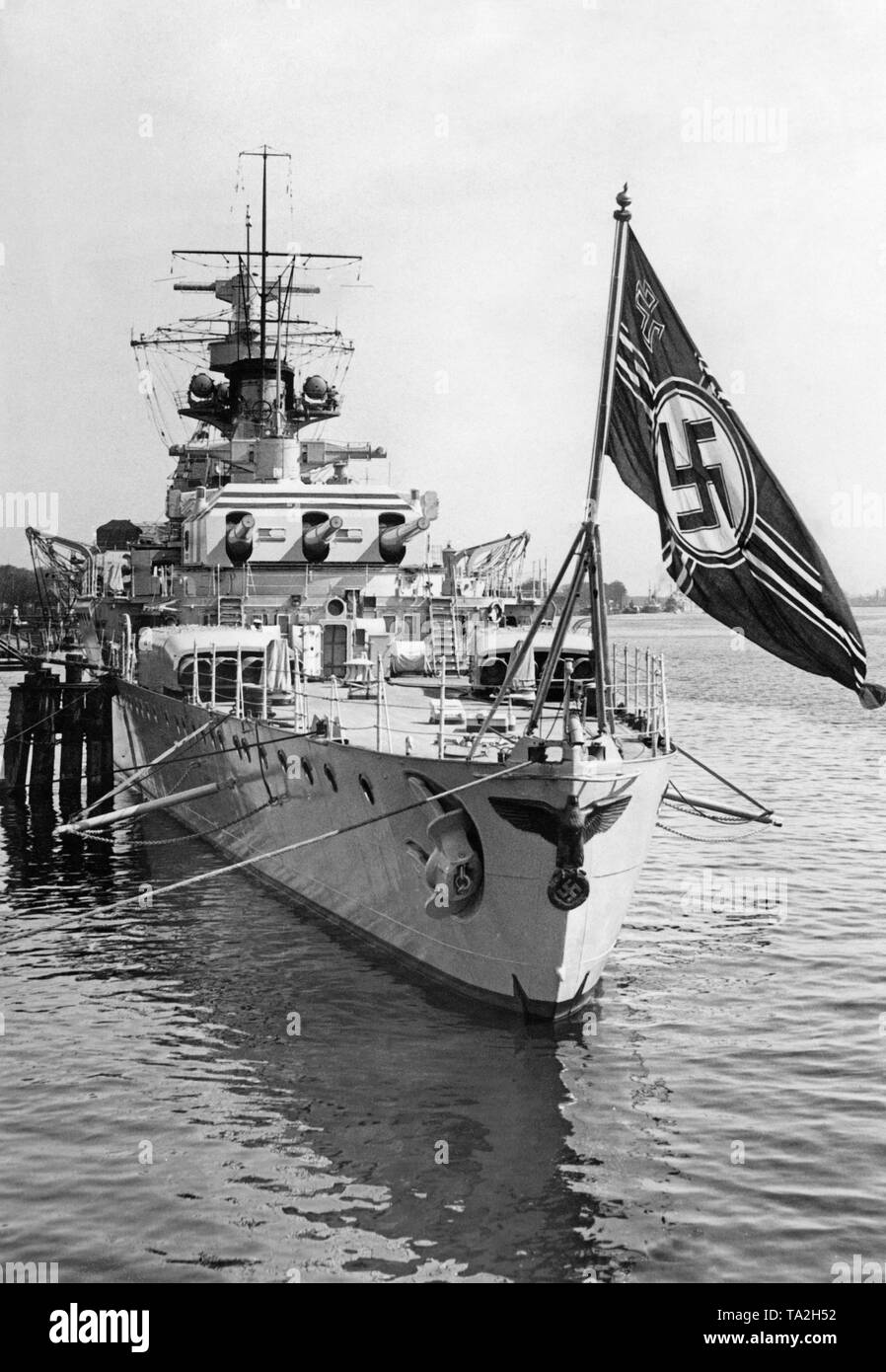 Photo of the rear of theheavy cruiser'Deutschland' at the great naval review in Swinoujscie (Poland) at the Szczecin Lagoon in the Baltic Sea. The warship is anchored in the harbor.  Here, the imperial eagle with a swastika, as well as the naval ensign of the German Reich at the stern. Behind, the rear turret with three 28 cm quick-firing guns. - Stock Image