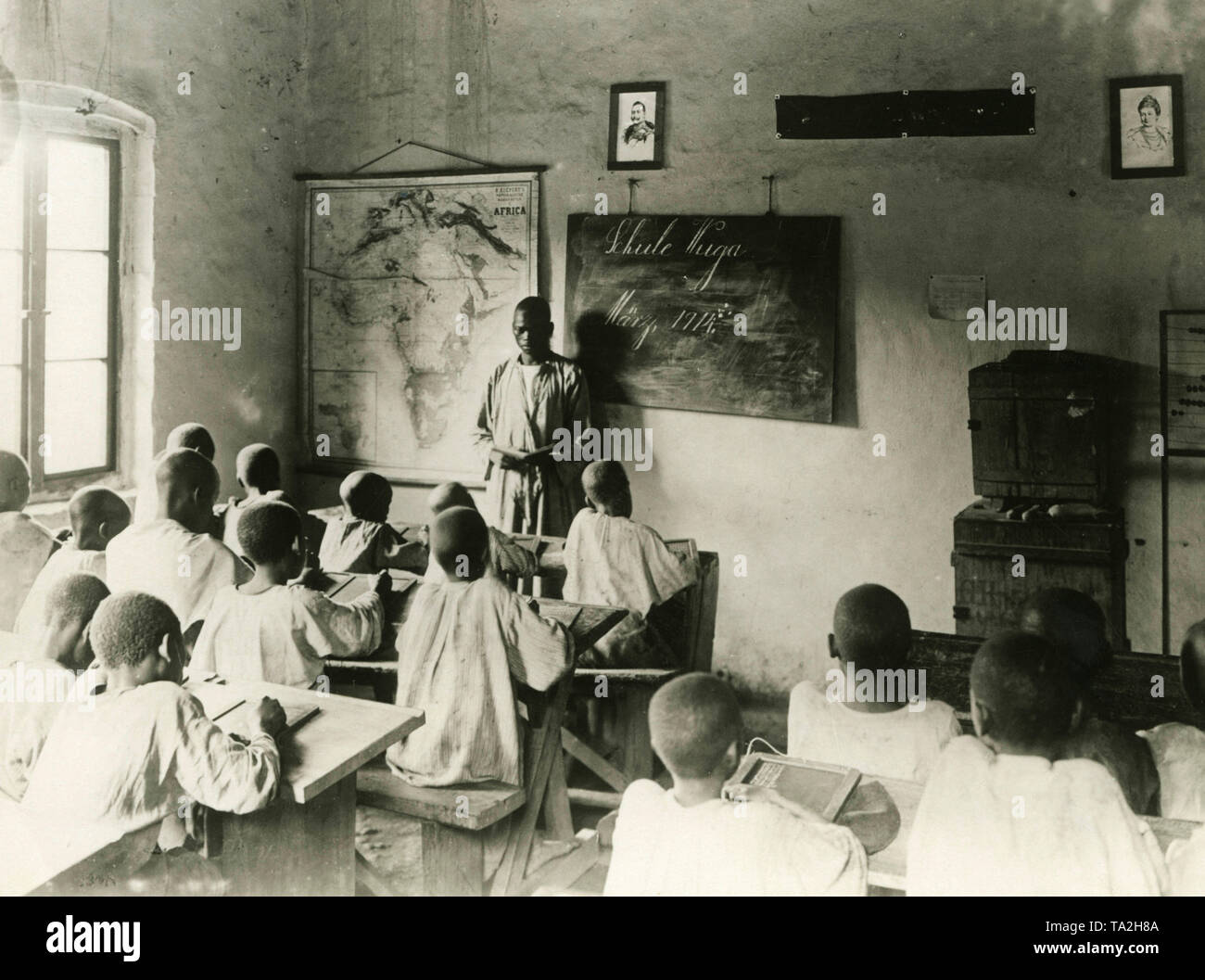 A black teacher in front of pupils in a classroom of the Evangelical mission station Wuga in Usambara in March 1914. On the wall are portraits of Emperor Wilhelm II and Empress Augusta Victoria. - Stock Image