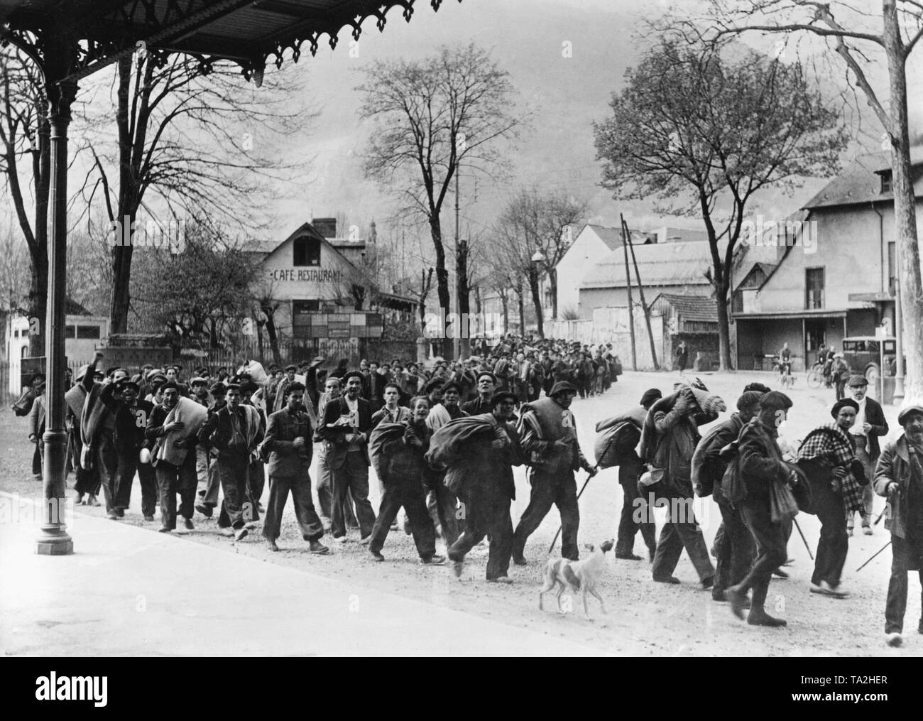 Photo of a column of former refugee Republican soldiers on the station square in the French Pyrenees-Bagneres-de-Luchon just behind the French-Spanish border. The men wear blankets, carry their luggage, and are already disarmed. They are watched by the inhabitants of Luchon. Photo from April, 1938. - Stock Image