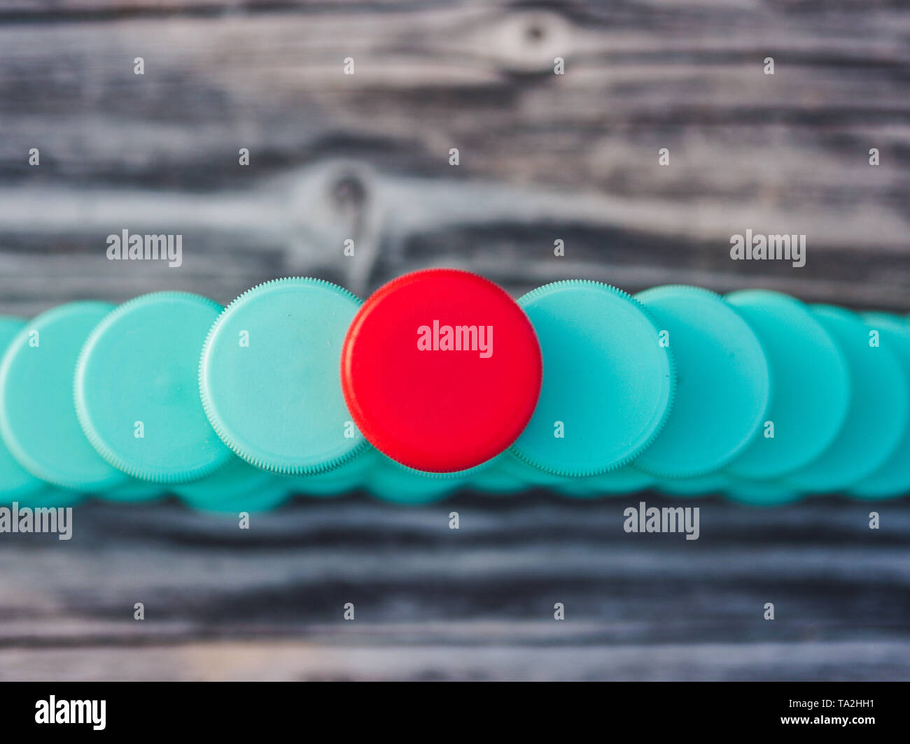 Image of different colored plastic caps on wooden background Stock Photo