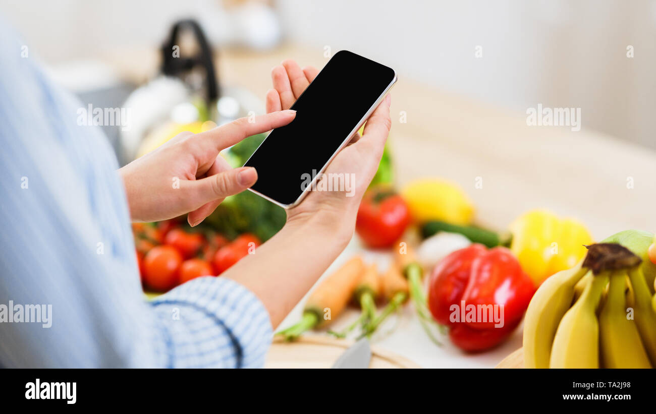 Search Recipe. Woman Using Smartphone Preparing For Cooking - Stock Image