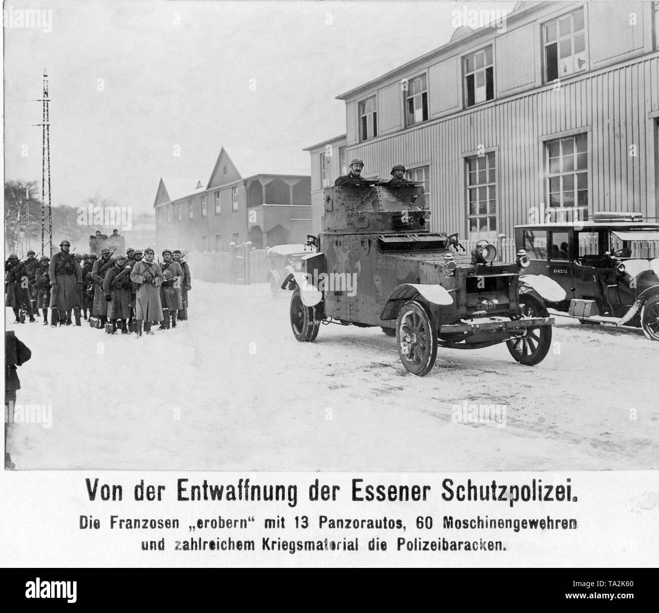 When the French invaded the Ruhr, the local police were also disarmed. Here an armored car of the occupation army rides in front of the barracks of the Essen police, in order to supervise the proper disarmament of the German policemen. - Stock Image