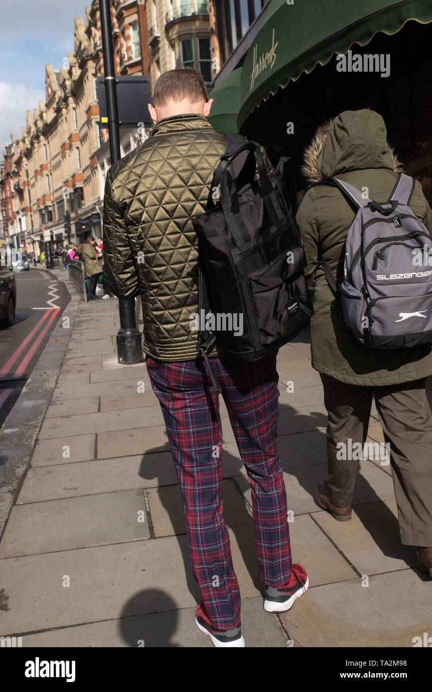 Bemannen Sie das Tragen der karierten Hose auf der Pflasterung außerhalb Harrods, London, Großbritannien. / Man wearing checkered trousers on the pave Stock Photo