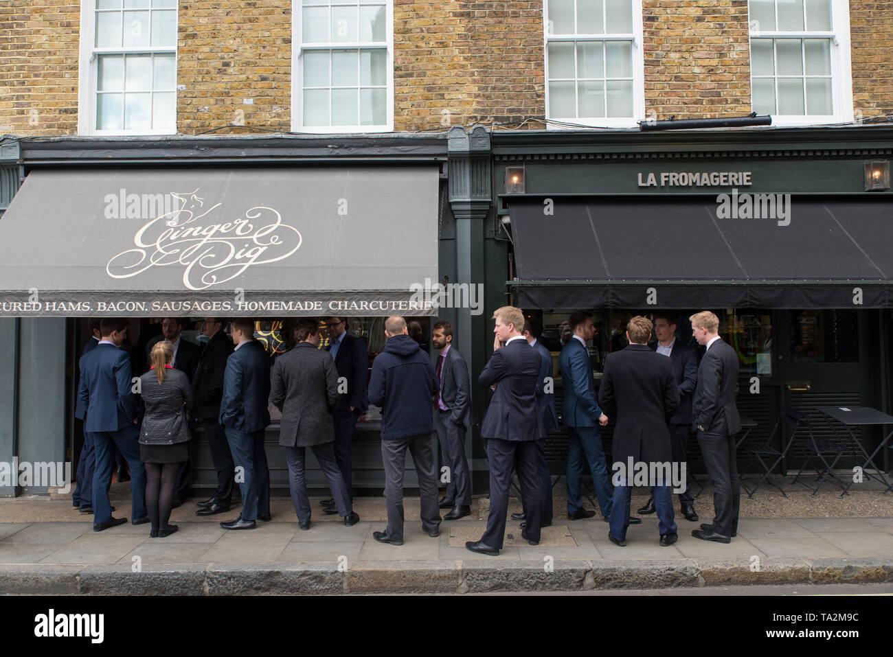 Junge Arbeiter stellen sich in der Metzgerei Ginger Pig auf, um eine Mahlzeit zu kaufen, Marylebone, London, Großbritannien. / De jeunes travailleurs  - Stock Image