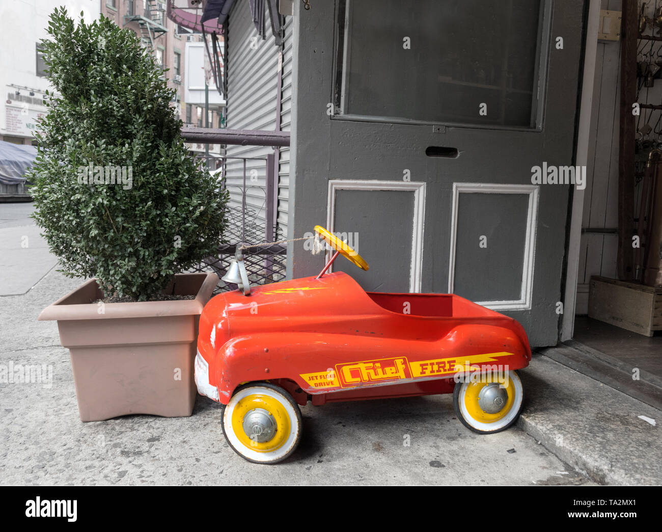 A bright red and yellow toy fire truck stands out againsta dreary grey concrete environment Stock Photo
