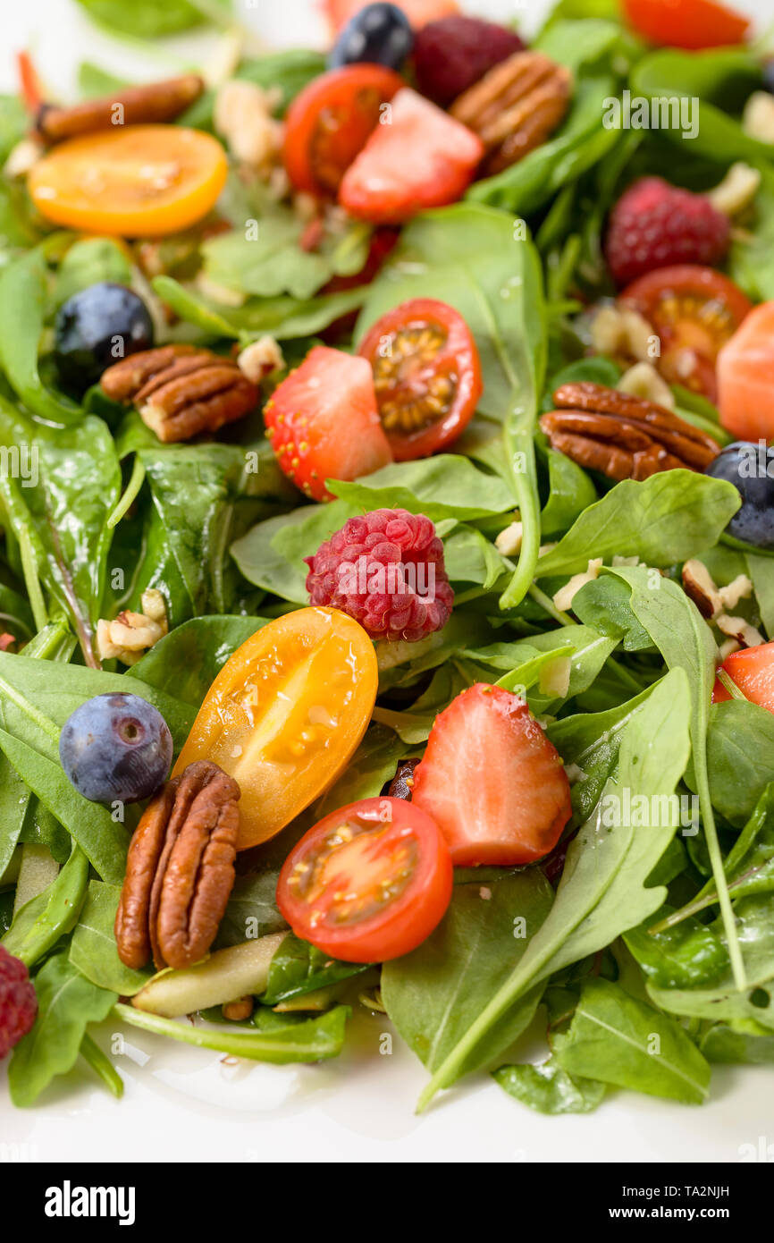 Green salad with raspberry, strawberry, blueberry and nuts. - Stock Image