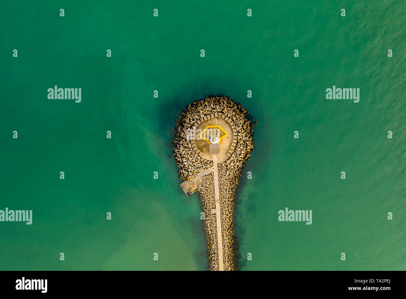 lignano sabbiadoro beacon lighthouse, view from a drone in a sunny day. green water and geometry lines - Stock Image