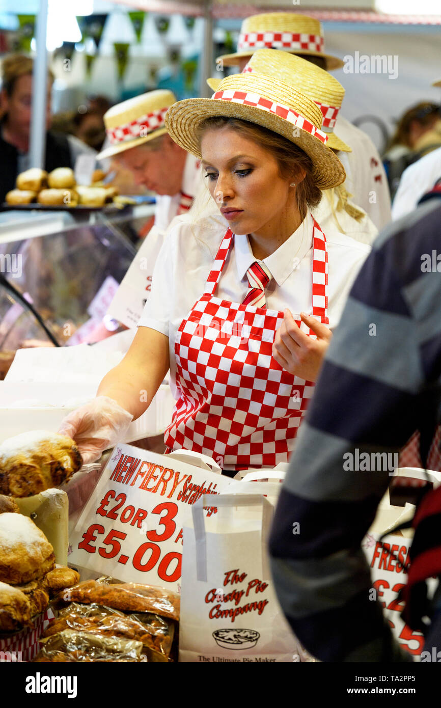 People (wearing red & white) working, display of pasties & pies & potential customers - Crusty Pie stall, Great Yorkshire Show, Harrogate, England, UK - Stock Image