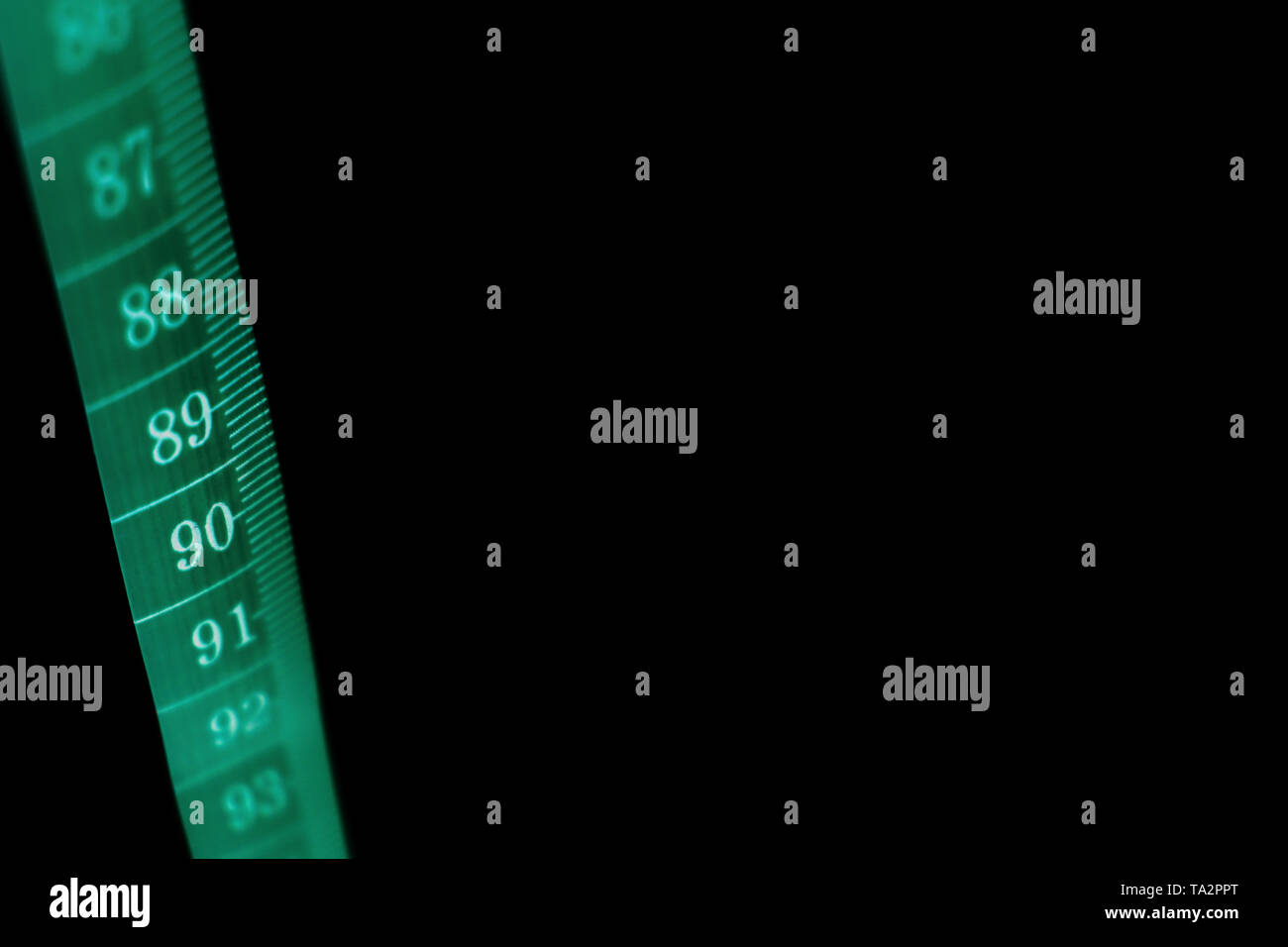 A concept black background with a  tape measure - Stock Image