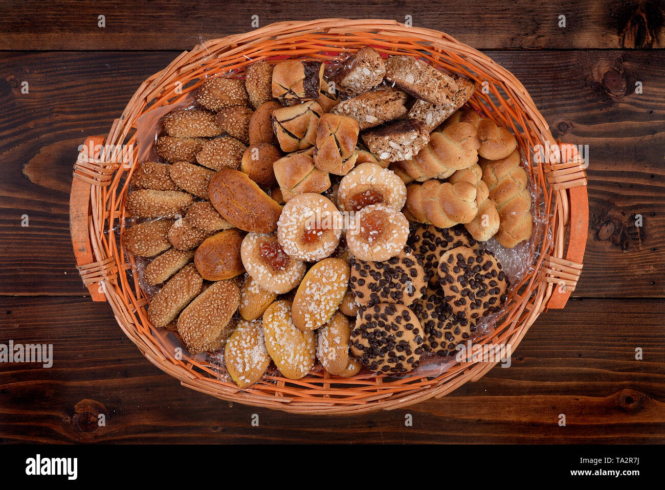 Basket with assortment of cookies on wooden board - Stock Image