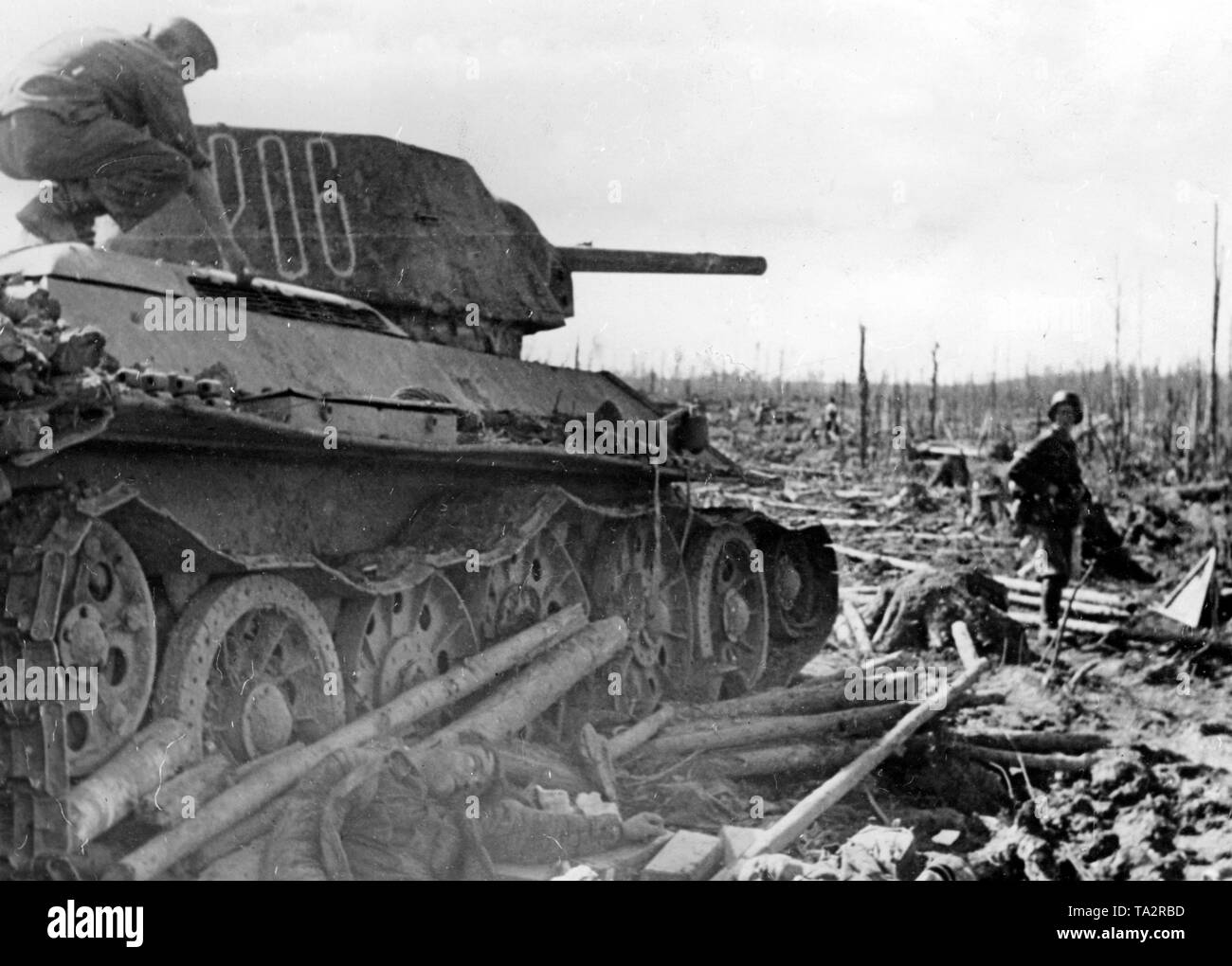 A German soldier climbs a shot down T-34 on the Volkhov Front. Next to it, a killed soldier lying on the ground. The fightings destroyed vast areas of the forest. Photo of the Propaganda Company (PK): war correspondent Schuerer. - Stock Image