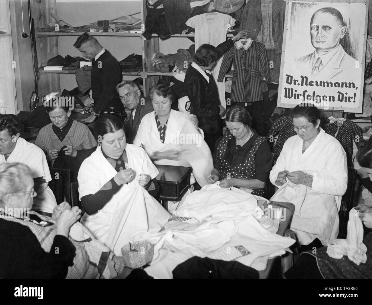 "Women and girls help in the tailoring rooms of the memellaendischen Winterhilfswerk. On the right a portrait of Ernst Neumann, beneath the slogan ""Dr. Neumann, we follow you!"" Stock Photo"