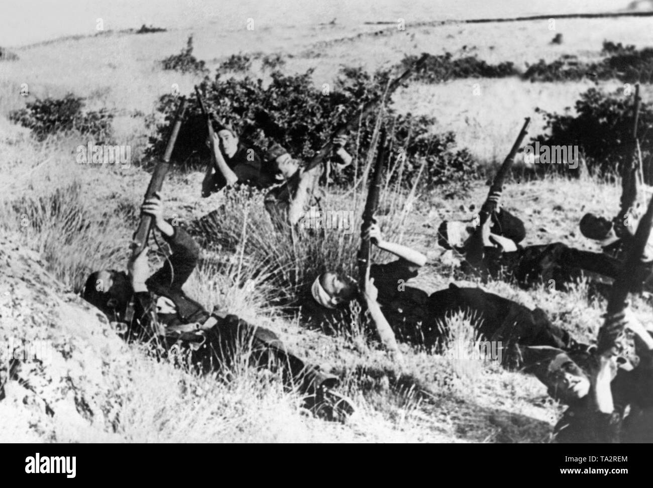 Photo of Republican fighters, who are trying to shoot at Spanish national warplanes with shotguns while lying on the ground at the Andalusian Front. - Stock Image