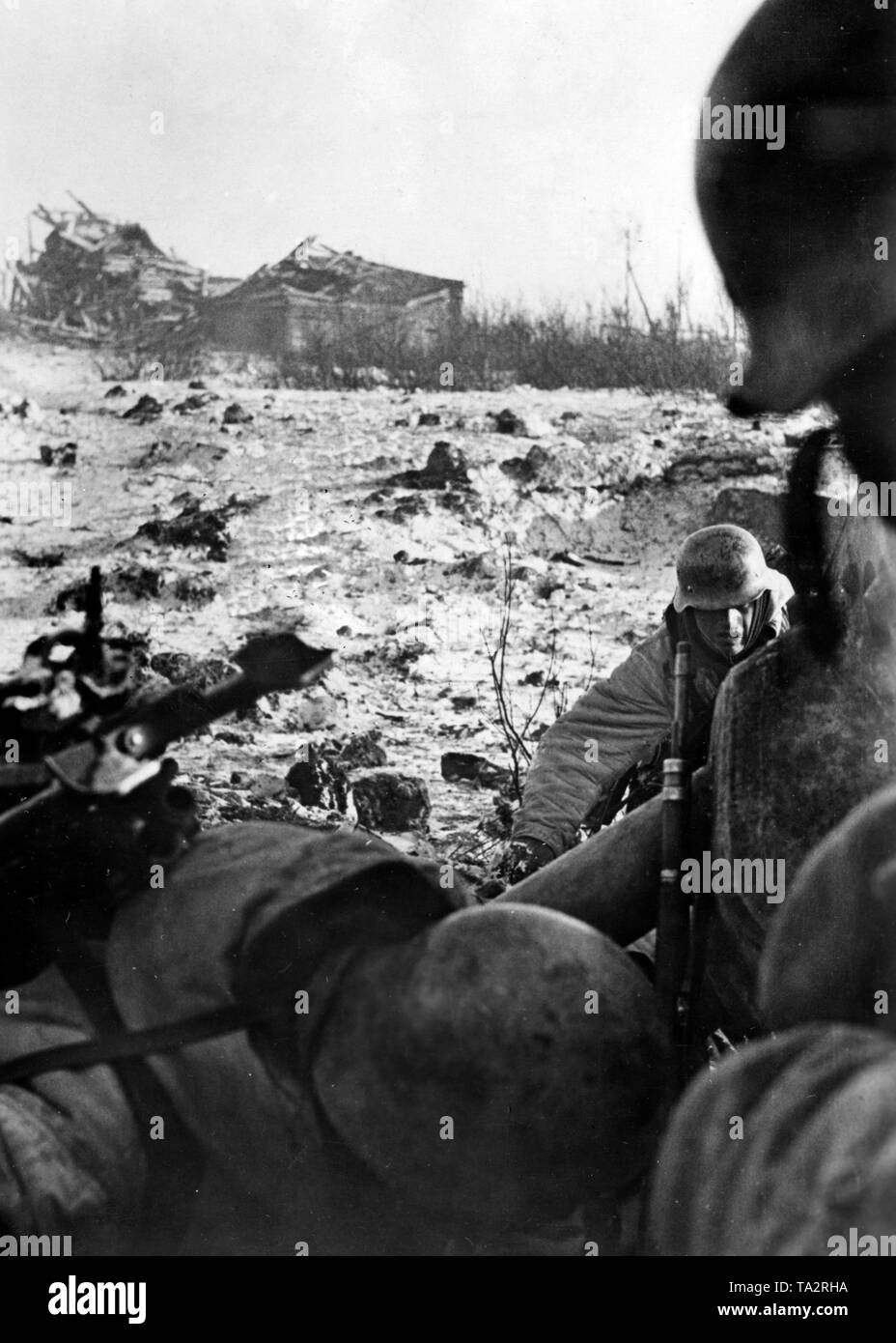 German soldiers take cover from Soviet artillery fire. The soil and the destroyed huts are proof of the violence of the battles. Photo of the Propaganda Company (PK): war correspondent Schuerer. Stock Photo