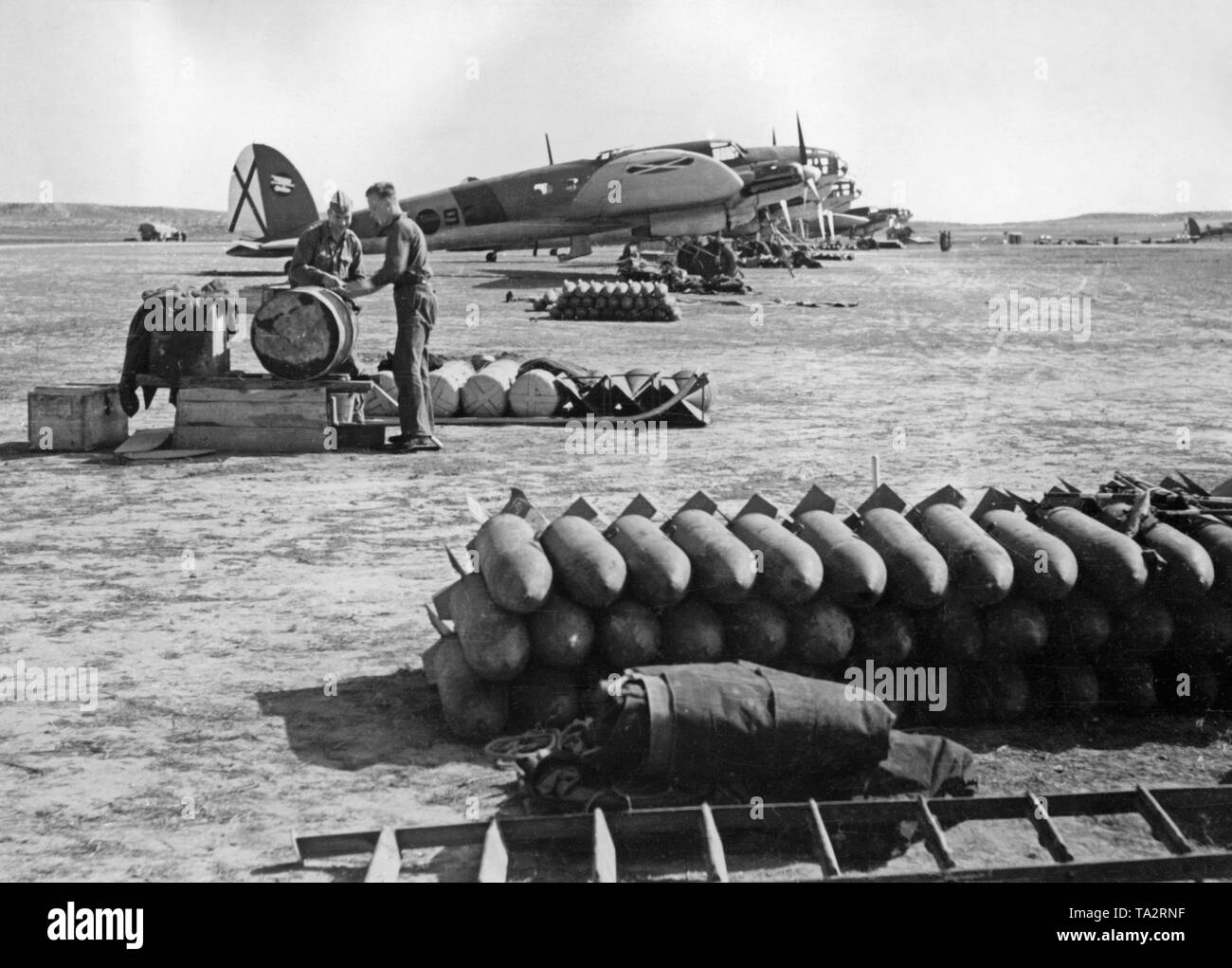 Photo of German Heinkel He 111 fighter bombers of the Condor Legion (Bomber group K / 88) on the airfield of Lerida, Catalonia, 1939. In the foreground there are grenades. Behind, ground personnel are working. The Saint Andrew's Cross of the Spanish Air Force is visible on the vertical tail. - Stock Image