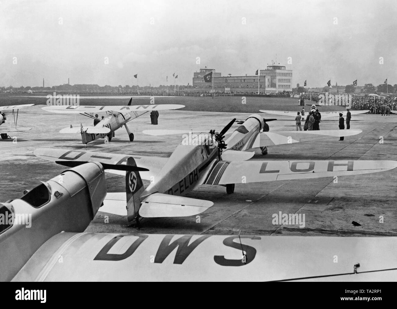 The German Aerobatic Championships, which were won by Wilhelm Stoer, takes place at the airport Oberwiesenfeld in Munich. Numerous spectators attend the event. - Stock Image