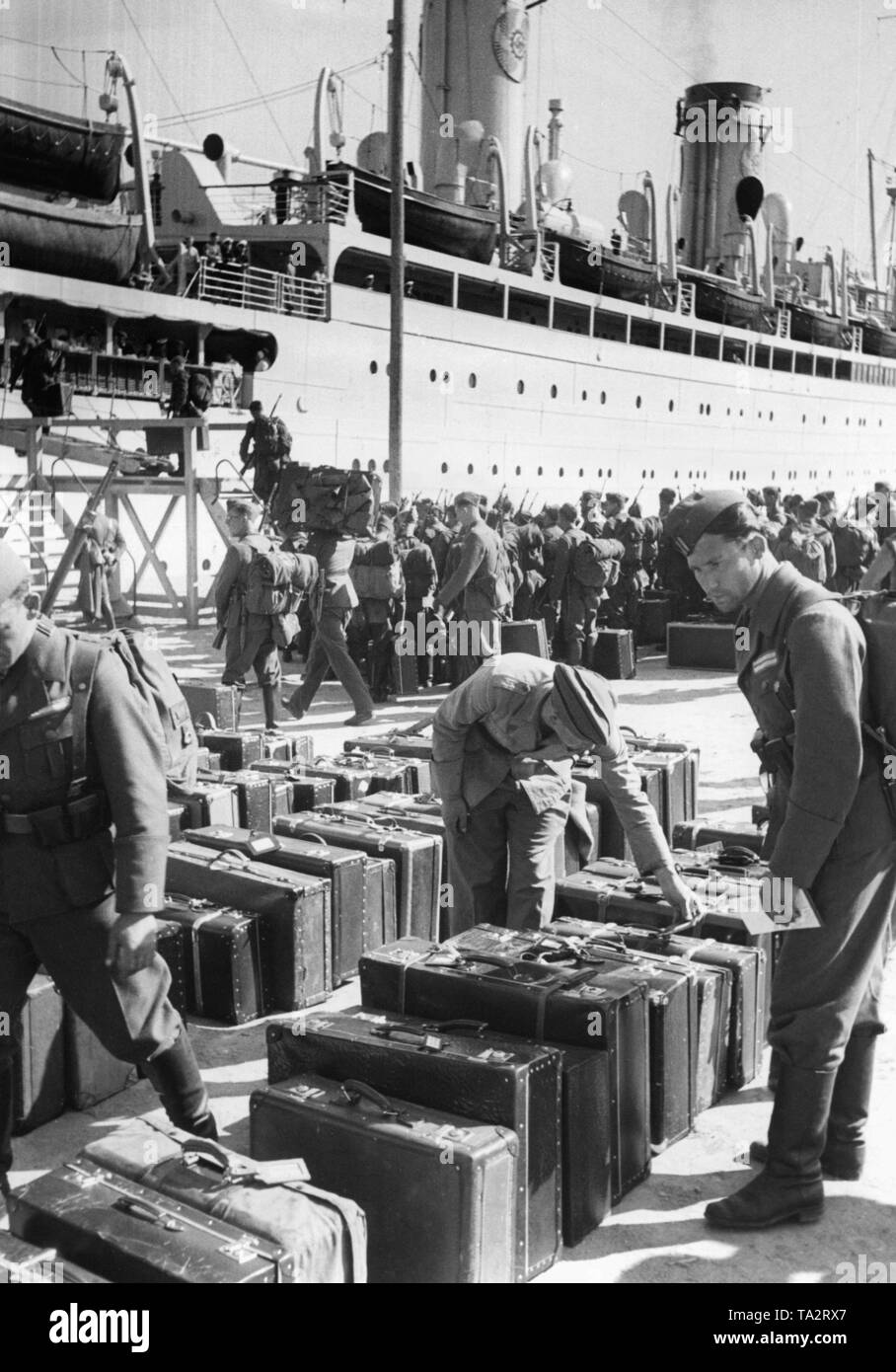 Photo of German soldiers of the Condor Legion during their return journey at the quay wall in the port of Vigo, Galicia on May 30, 1939. In the background, the Kraft durch Freude ('Strength through Joy') steamboat (KdF-fleet), 'The German' ('Bremer Vulkan', 1924, previously 'Sierra Morena'), which was to take the Spanish fighters home. At the front, the luggage of the soldiers. - Stock Image