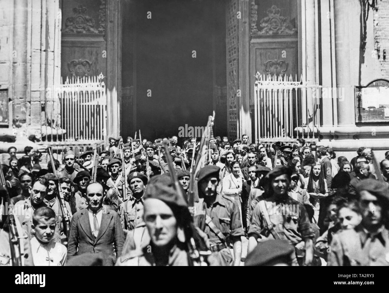 Volunteer Spanish national supporters (armed, in uniform or civilian clothes with banners) leave a service in the Cathedral of Zaragoza (Catedral-Basilica de Nuestra Senora del Pilar de Zaragoza) through the main portal before their departure to the front. The Republicans tried to invade Zaragoza in vain in July, 1936. A further offensive failed in September, 1937. Stock Photo